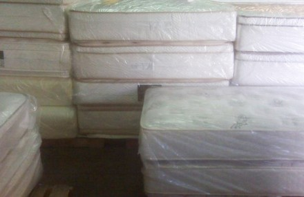 Mattresses covered in plastic.