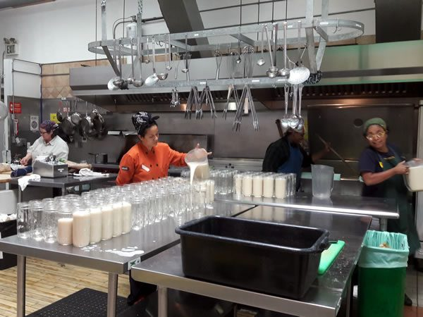 Three Stone Hearth employees filling mason jars